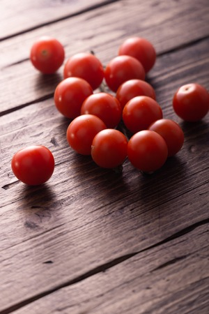 Fresh ripe garden tomatoes on wooden table. Side view with copy space.