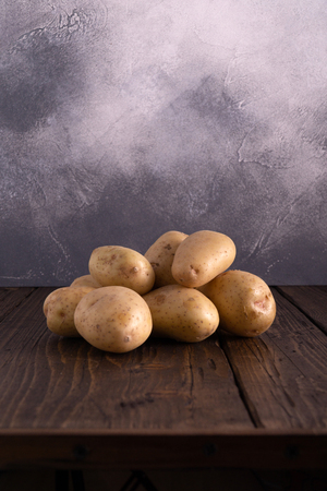 Heap of fresh potatoes on rustic wooden surface and slate textured background. Organic food, carbs, tubers.