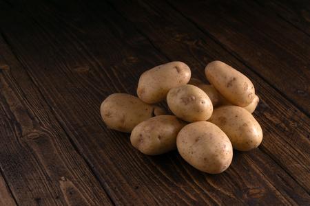 Heap of fresh potatoes on rustic wooden surface. Organic food, carbs, tubers. Banco de Imagens
