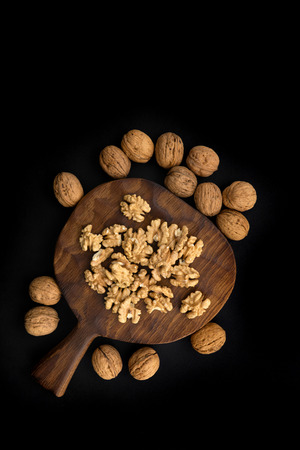 Cracked and whole walnuts on wooden cutting board and black table, top view. Healthy nuts and seeds composition.