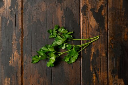 Manojo de perejil verde sobre mesa rústica de madera. Vista superior.