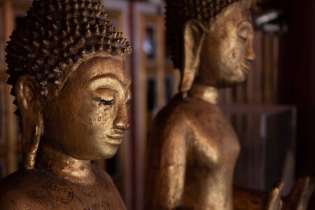 Aged time-worn bronze Buddha statues facing light. Stockfoto
