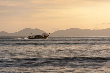 Traditional long boat sailing by the island in the evening, Thailand.