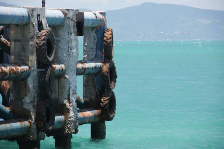 Pier for ferry dock with black tires used as boat bumper. Emerald water and island on horizon.