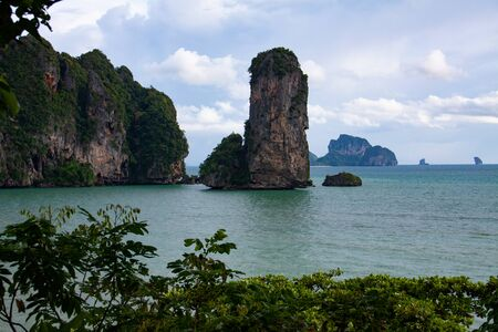 Picturesque beach with a view on the huge rock formation, sea view of Andaman sea and sand, iconic sight in Krabi province, Thailand.