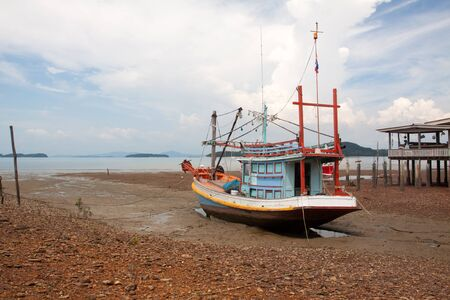 FIshing boat and wooden house at low tide beach, Phangan island, Thailand. Imagens
