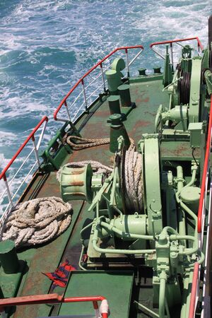 Ferry boat deck equipment with thick mooring rope and blue sea water wave, Thailand.