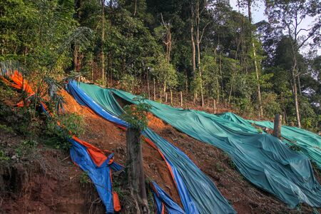 Slope protection with huge plastic sheet to avoid soil erosion when it rains. Colorful pieces of plastic cover lying on the slope.