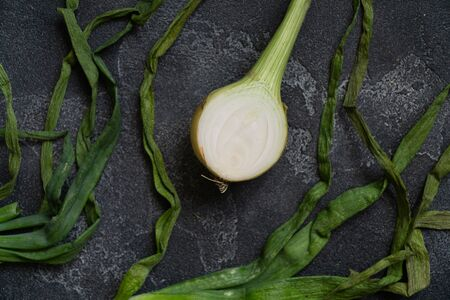 Organic onion with leaves on dark textured surface. Onions background. Bulb onions, green spring. Top view. Stock fotó