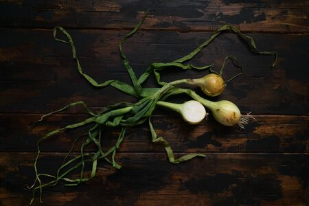 Organic onions with leaves on rustic wooden table. Food background. Bulb onions, green spring. Top view. Stock fotó