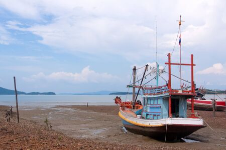 Traditional Thai fishing boats on a beach during low tide, Phangan island, Thailand.