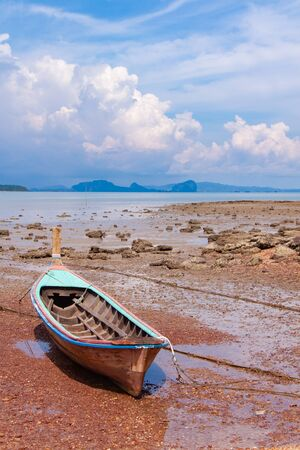 Traditional longtail boat on the sand beach at the low tide. Sea view with islands on horizon and clouds in the sky.