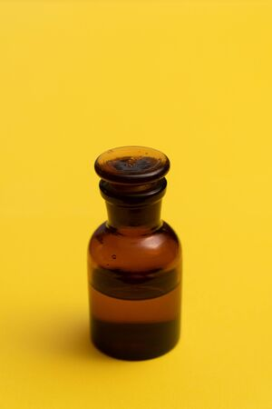 Glass bottle on yellow background. Perfume, medicine, chemistry background.