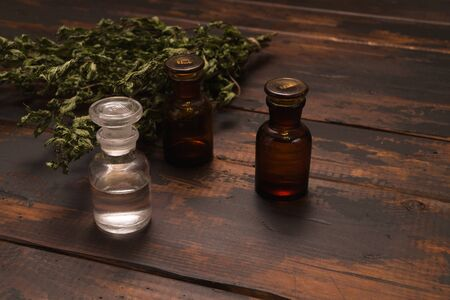 Small bottles on a wooden surface with dried herbs. Autumn still life composition. Фото со стока