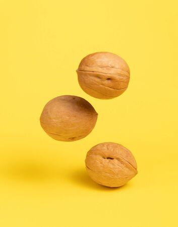 Delicious flying walnuts on yellow background.