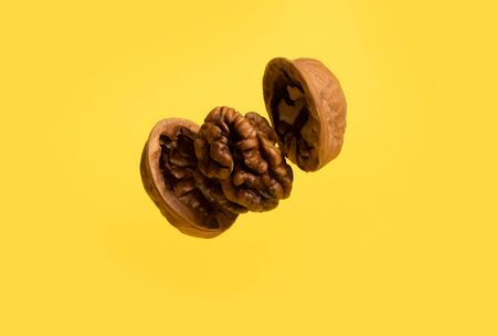 Delicious flying walnut on yellow background.