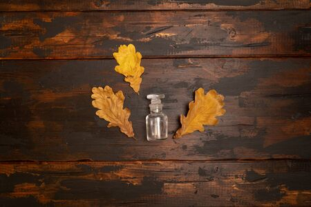 Small bottle on a wooden surface with dried oak tree leaves. Autumn still life composition.
