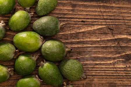 Feijoa fruits lying on textured wooden surface. Background, banner, header Фото со стока