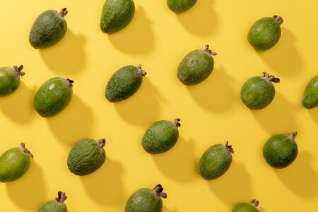 Fruit pattern of fresh feijoa fruits against yellow background. Top view pop art minimal flat lay style. Фото со стока