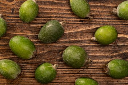 Feijoa fruits lying on textured wooden surface. Background, banner
