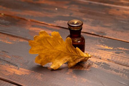 Small bottle on a wooden surface with dried oak tree leaf. Autumn still life concept. Banco de Imagens