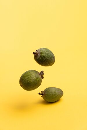 Feijoa fruits floating in the air on yellow background