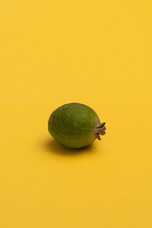 Fresh feijoa fruit on bright yellow surface. Studio close-up shot.