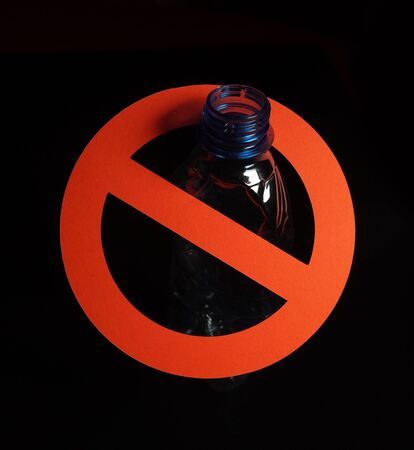 Empty blue plastic bottle in a stop sign on black background. Concept of stop plastic pollution, recycling plastic, plastic free.