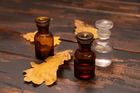Small bottles on a wooden surface with dried oak tree leaves. Autumn still life composition.