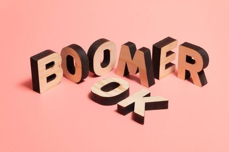 OK Boomer. Internet meme popular among young people. Wooden words on pink background.