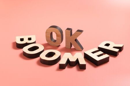 OK Boomer. Internet meme popular among young people. Wooden words on pink background. Stock Photo