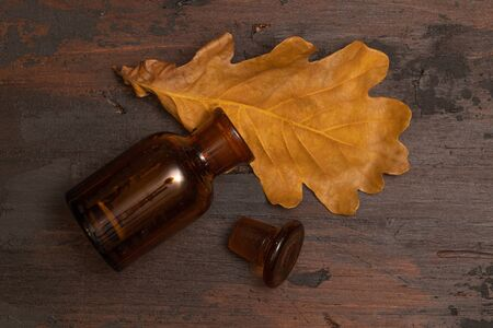 Small bottle on a wooden surface with dried oak tree leaf. Autumn still life