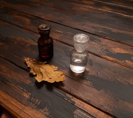 Small bottles on a wooden surface with dried oak tree leaf. Autumn still life composition.