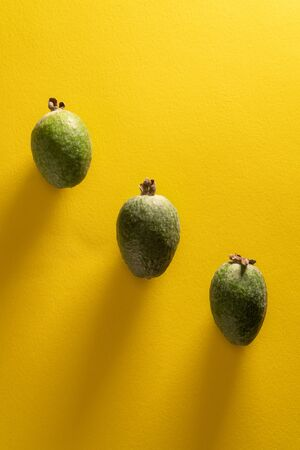 Three fresh feijoa fruits against yellow background. Top view pop art minimal flat lay style. Фото со стока