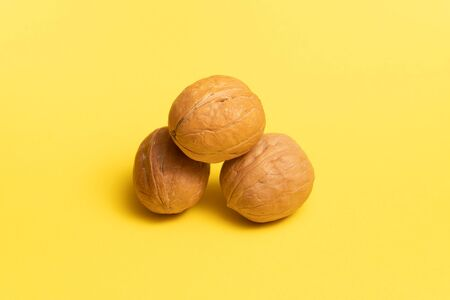 Delicious walnuts on yellow background.