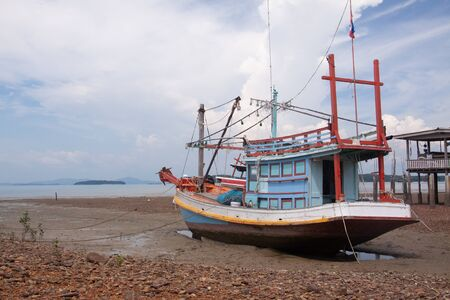 FIshing boat and wooden house at low tide beach, Lanta island, Thailand.