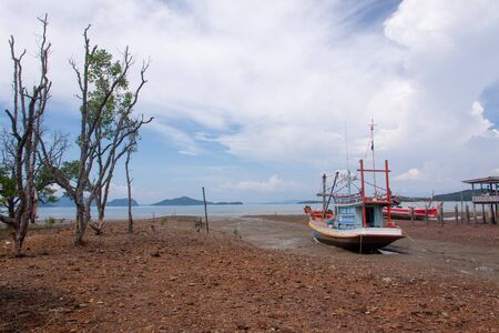 Scenic sea view with fishingboats, wooden house, and trees during low tide on Lanta island, Thailand. Фото со стока