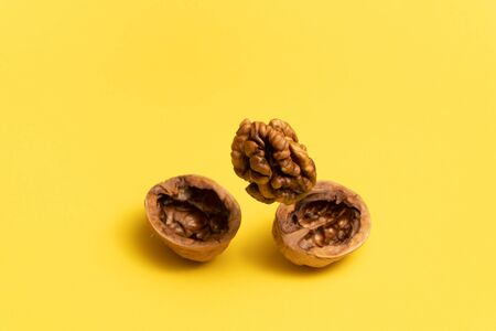 Delicious flying walnut on yellow background. Фото со стока