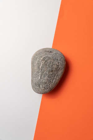 Pebble stone on white and orange paper background. Flat lay, top view, minimal design template with copyspace.