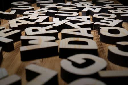 Heap of wooden letters are lying on the wooden board Reklamní fotografie