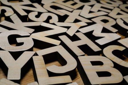 Random wooden letters lying on wooden background.
