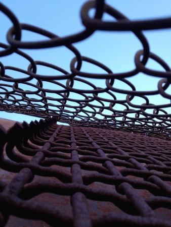 chainlinked: Bekijk in de blauwe door de zwemvliezen keten verbonden hek Stockfoto