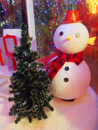 beside: Snowman with gifts beside christmas tree