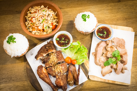 Thai style food : Papaya  salad  , Grilled chicken , Grilled pork and sticky rice on wooden background Stock Photo