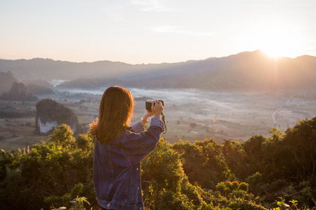 Young woman taking photos of sunrise in mountain at Phu Lung ka,Thailand