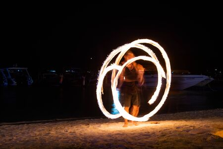 Amazing fire dancers Swing fire dancing show fire show on the beach  in Thailand Stock Photo