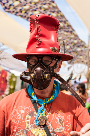 man in a leather mask and a red hat