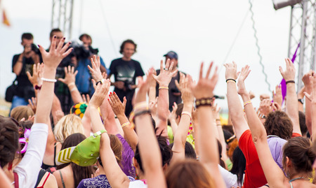 the crowd at the concert pulls his hands up