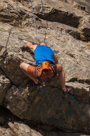 Male rock climber climbs a steep rock photo