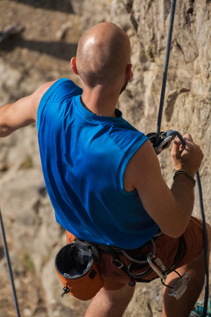 Close-up of Male rock climber climbs a steep rock photo